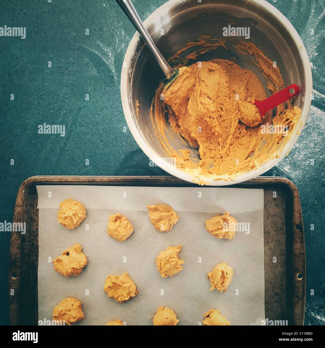Making pumpkin cookies flat view showing stainless steel mixing bowl full of cookie batter and parchment paper lined - Stock Image