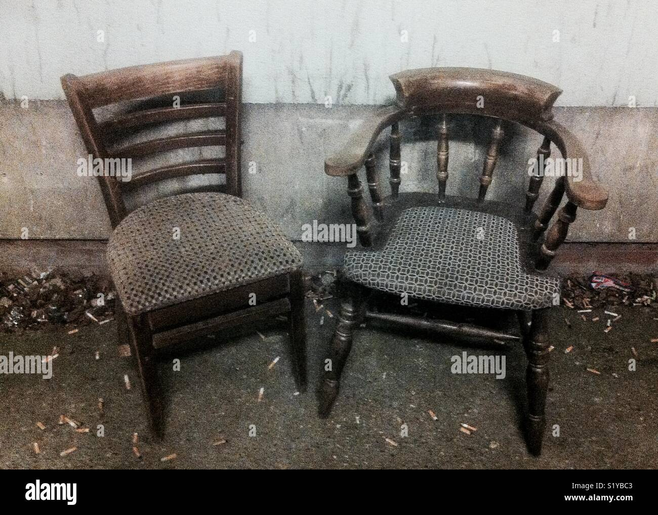 Empty chairs and fag butts in a derelict pub from yesteryear. - Stock Image