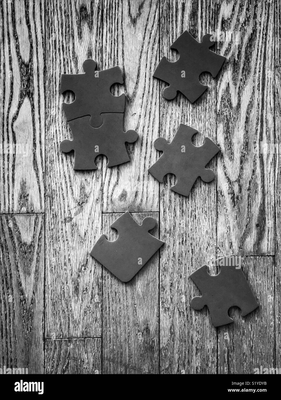 Six Plain Puzzle Pieces On A Wooden Floor In Black And White Stock