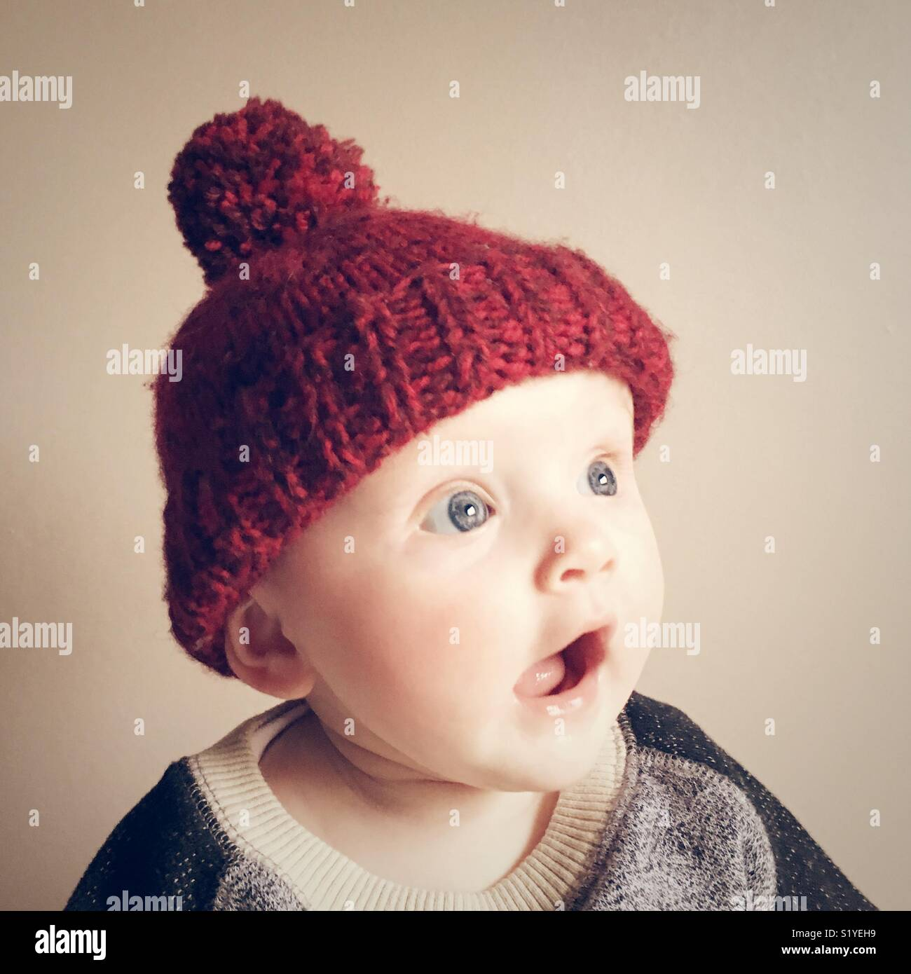 Baby wearing a red woolly hat - Stock Image