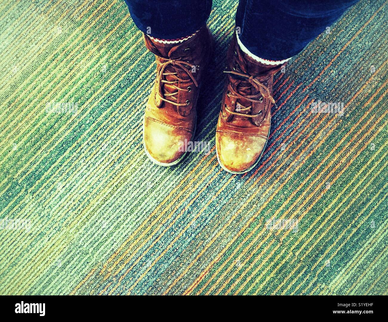 Looking down at person's feet wearing scuffed, old, brown work boots on a multicoloured carpet - Stock Image