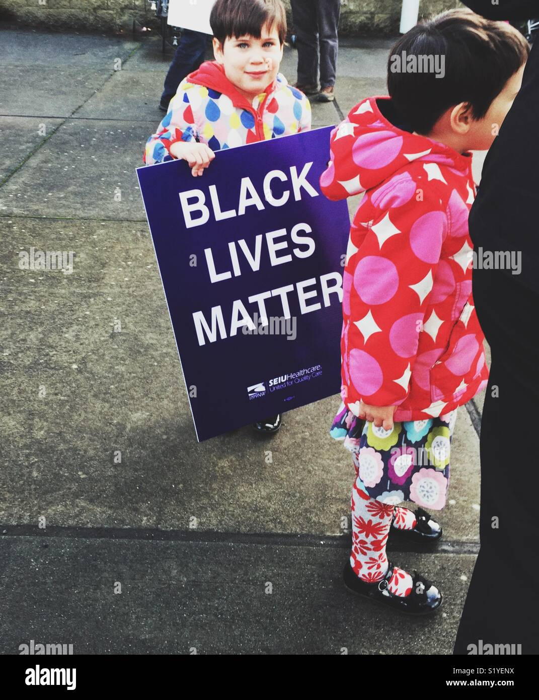 A young child holding Black Lives Matter sign on the street during protest march in Seattle - Stock Image