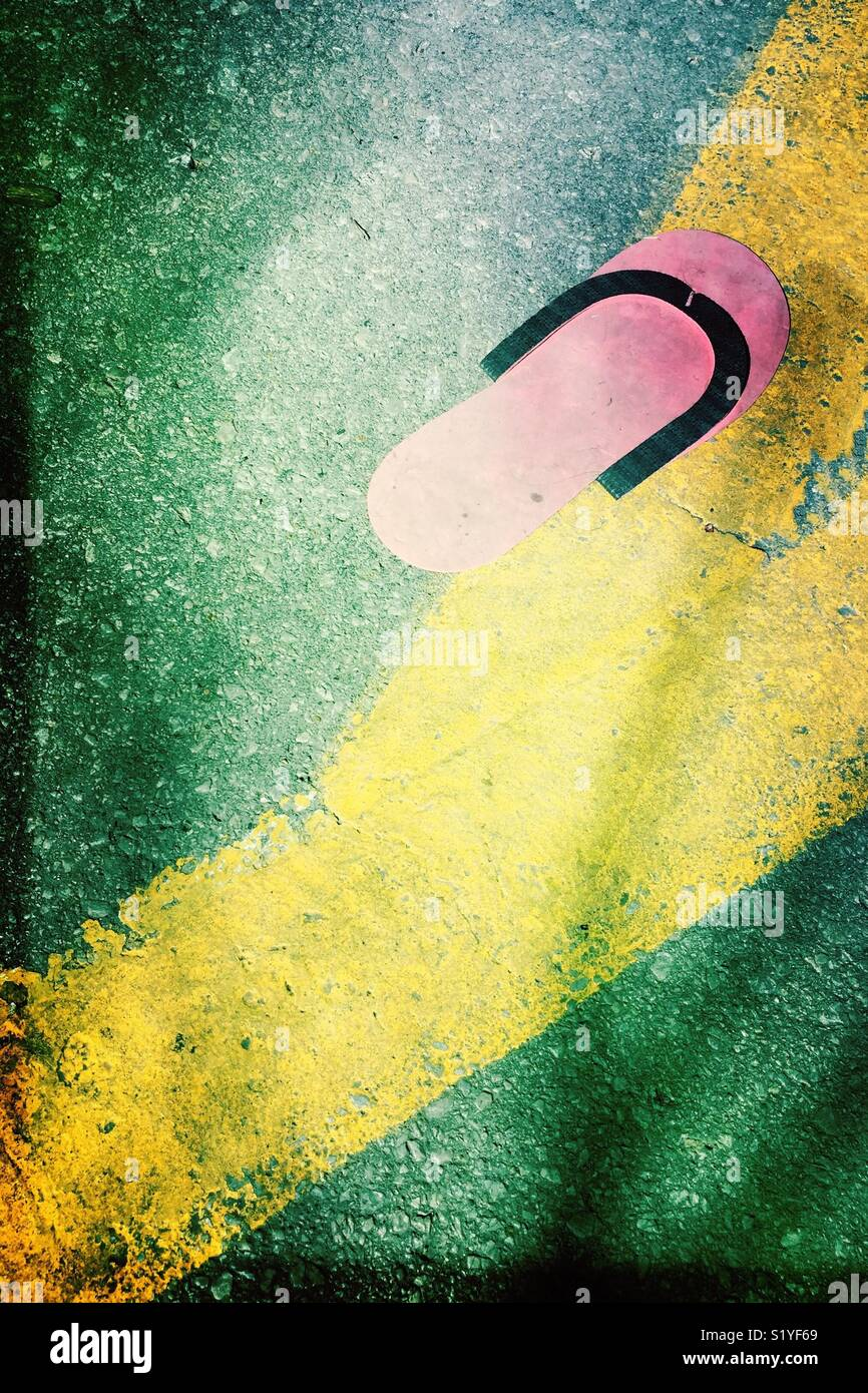 A very flat, pink flip flop that was discarded in a parking lot. - Stock Image