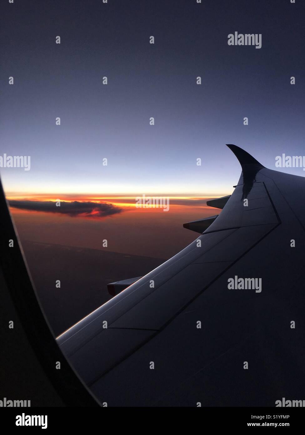 Flying above Thailand. Beautiful sunrise through the aeroplane window. Jan 2018 - Stock Image