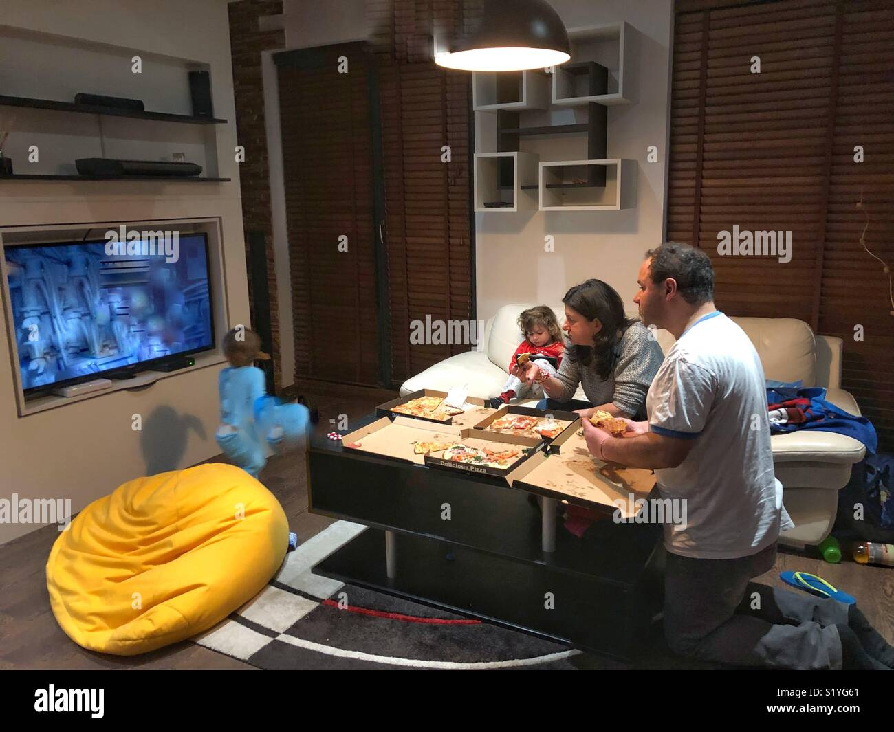 Family eating pizza at home - Stock Image