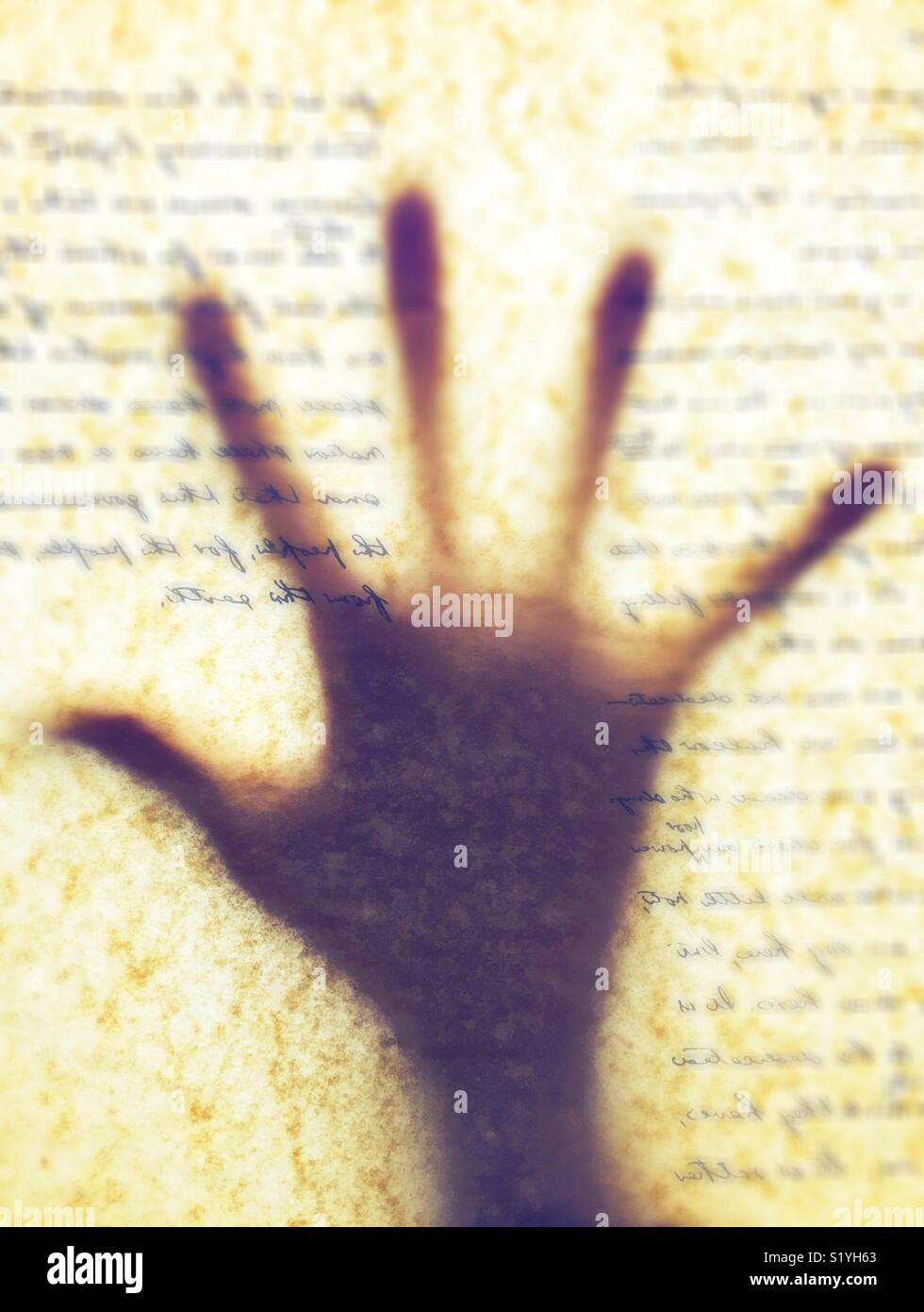 Silhouette of a hand against words on parchment paper. - Stock Image