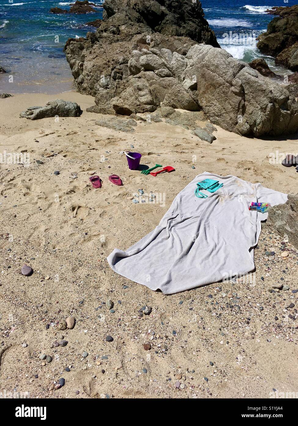 A day at the beach, near waters edge a still life with towel and beach shoes and toys - Stock Image