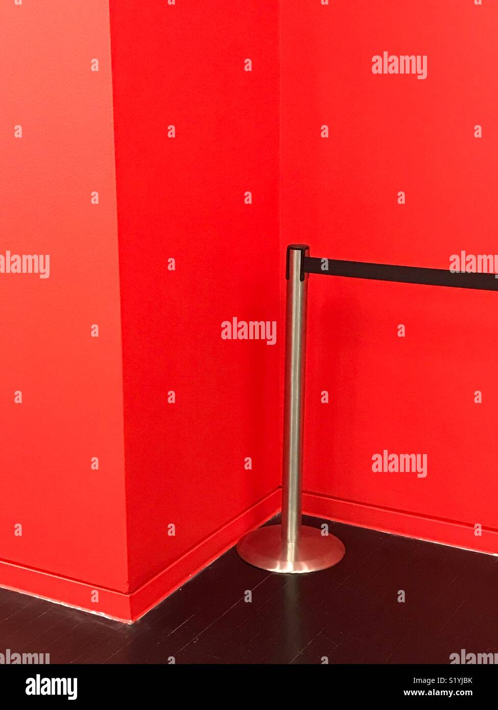 A barrier and a red wall - Stock Image