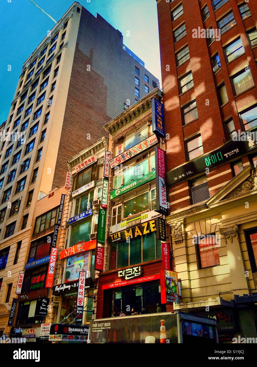 Brightly colored storefronts with multi lingual signage in Koreatown, W. 32nd St., New York City, USA - Stock Image
