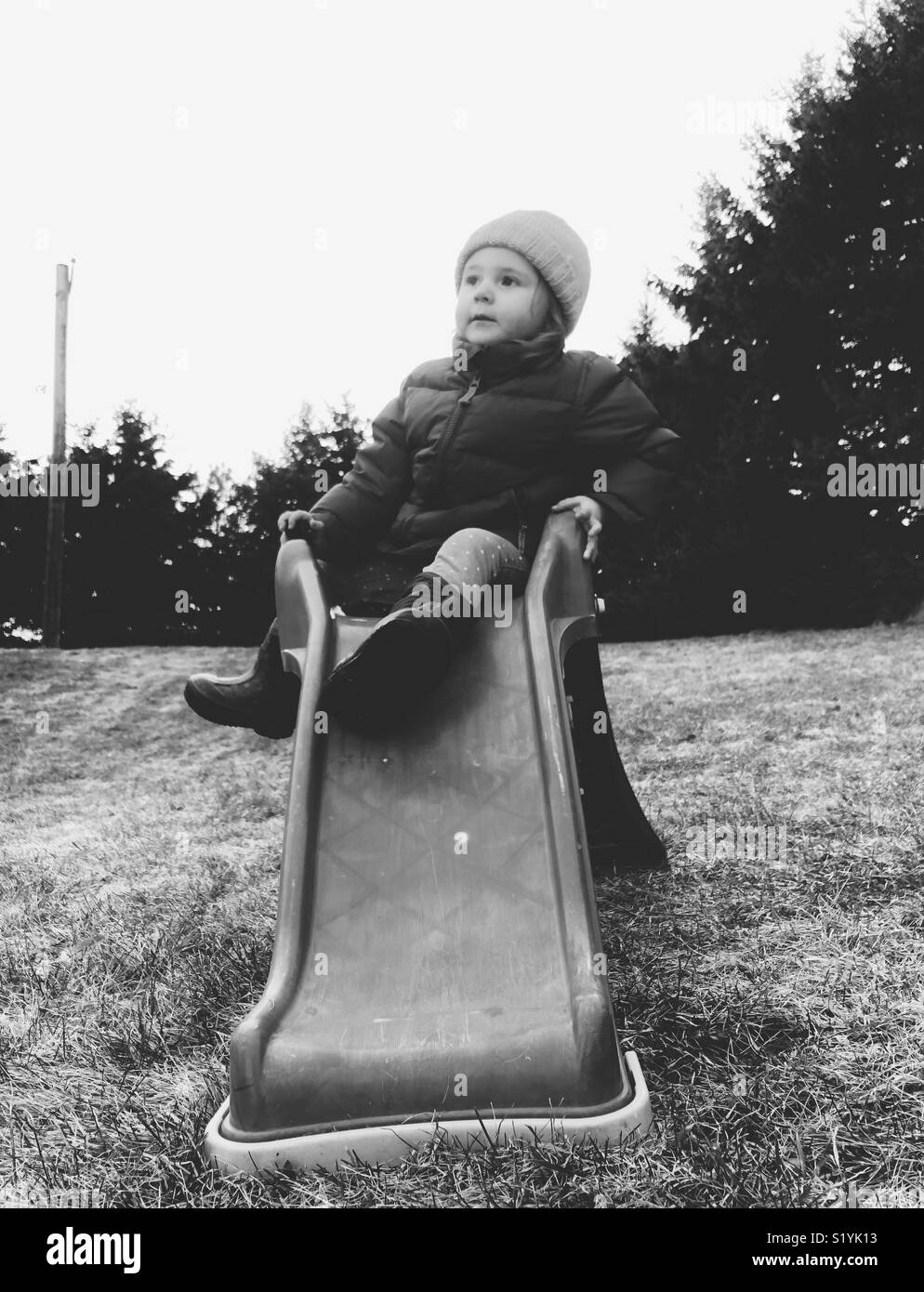 Black and white image of toddler girl sitting on plastic slide in backyard garden - Stock Image