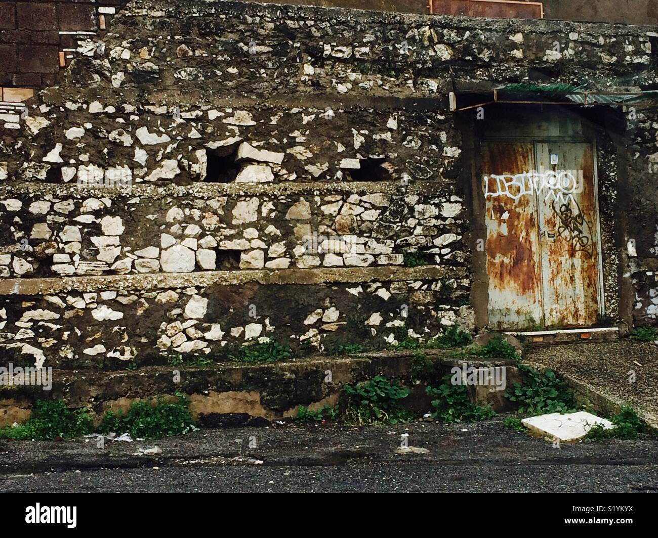 Old, ruined wall and door, suburban area - Stock Image