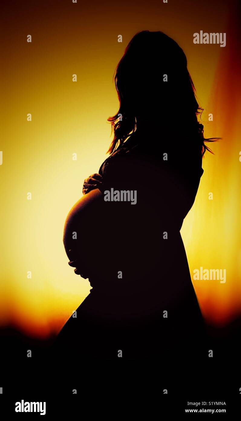 Silhouette of a pregnant women in the sun set - Stock Image