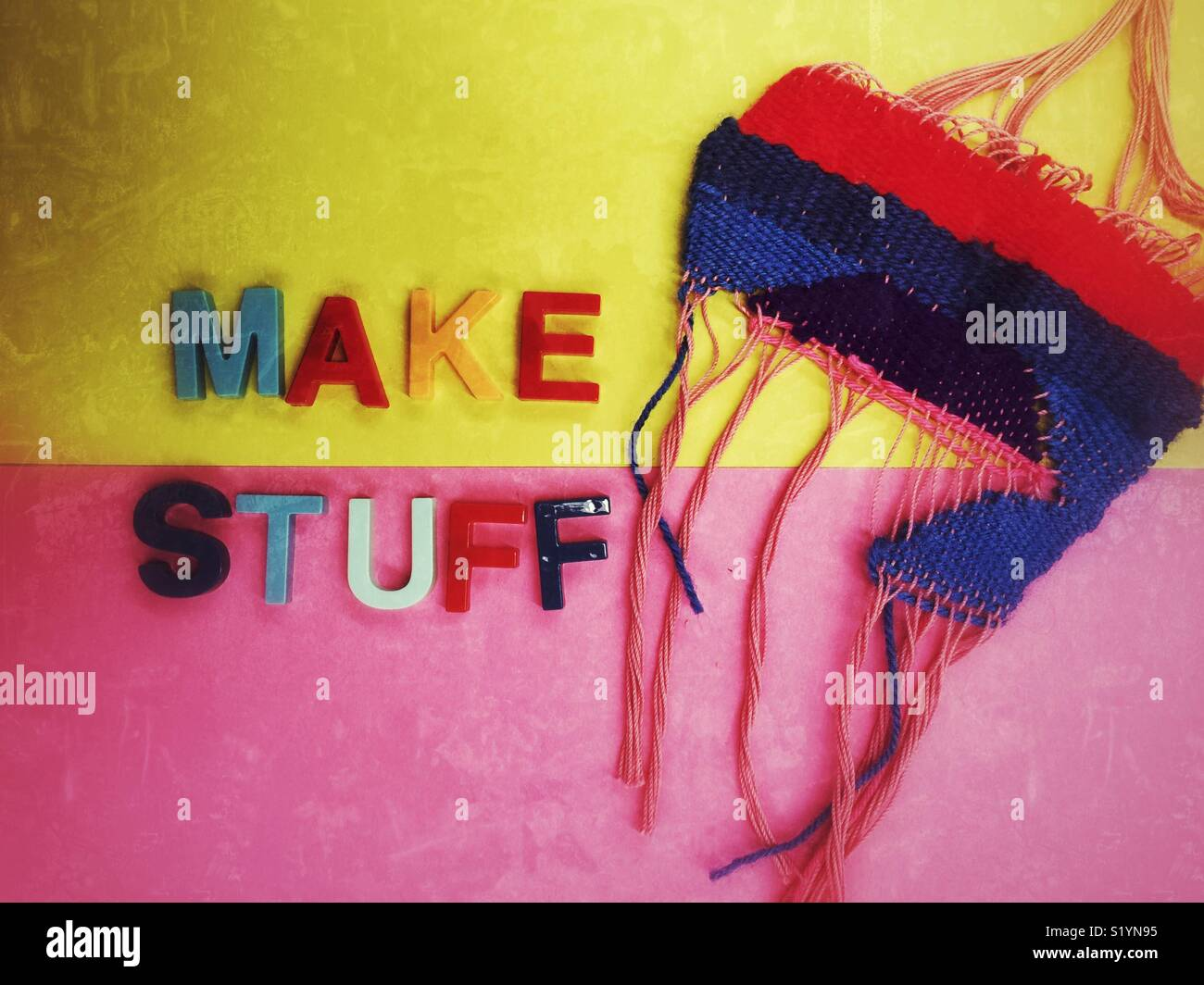 Woven artsy tapestry next to the words Make Stuff in magnetic fridge letters on duotone yellow and pink background - Stock Image