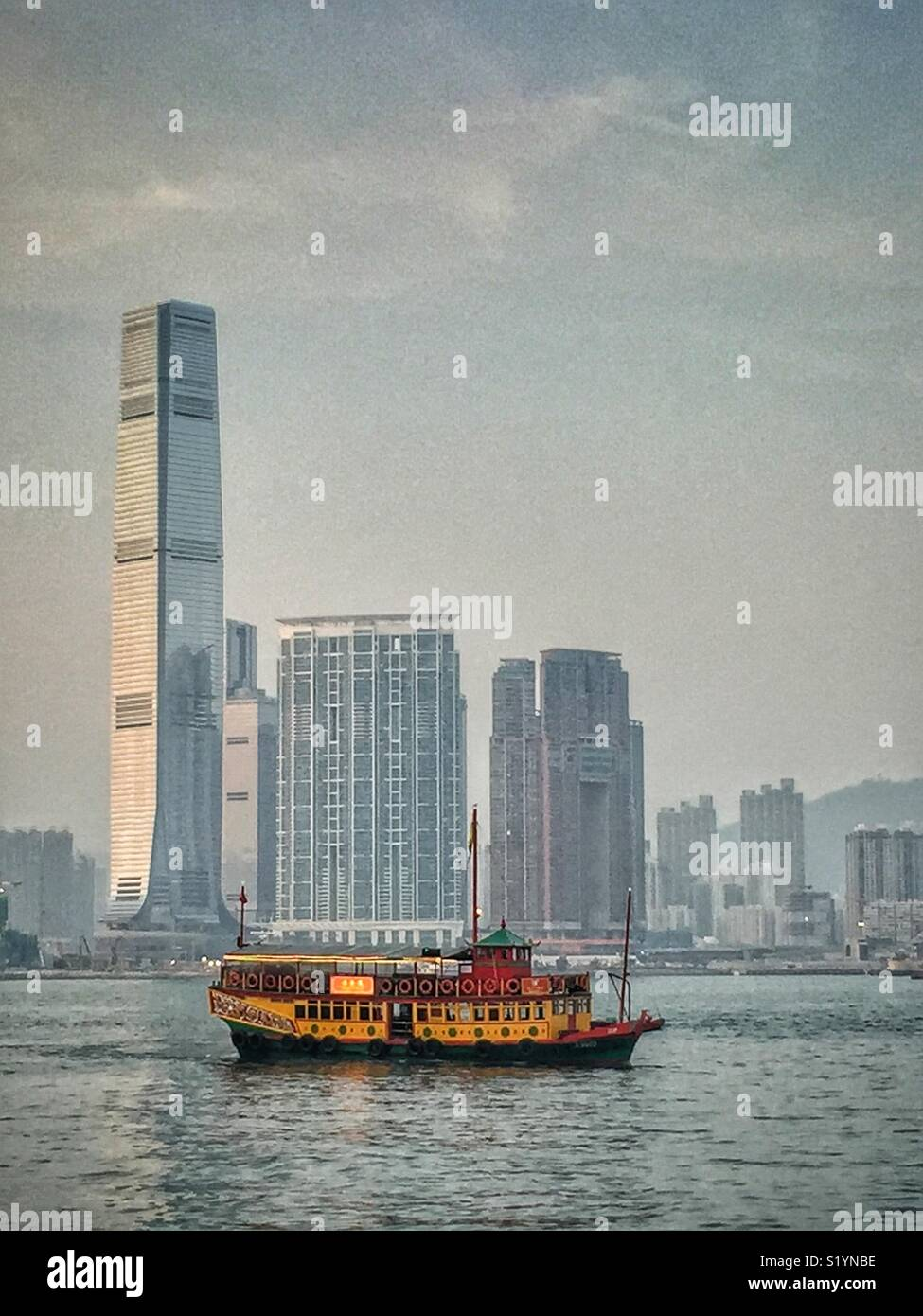 The 'Wing On Travel', a double decker Chinese junk, carrying tourists on a sightseeing cruise on Victoria Harbour at twilight, in front of the ICC, Hong Kong's tallest skyscraper, in West Kowloon - Stock Image
