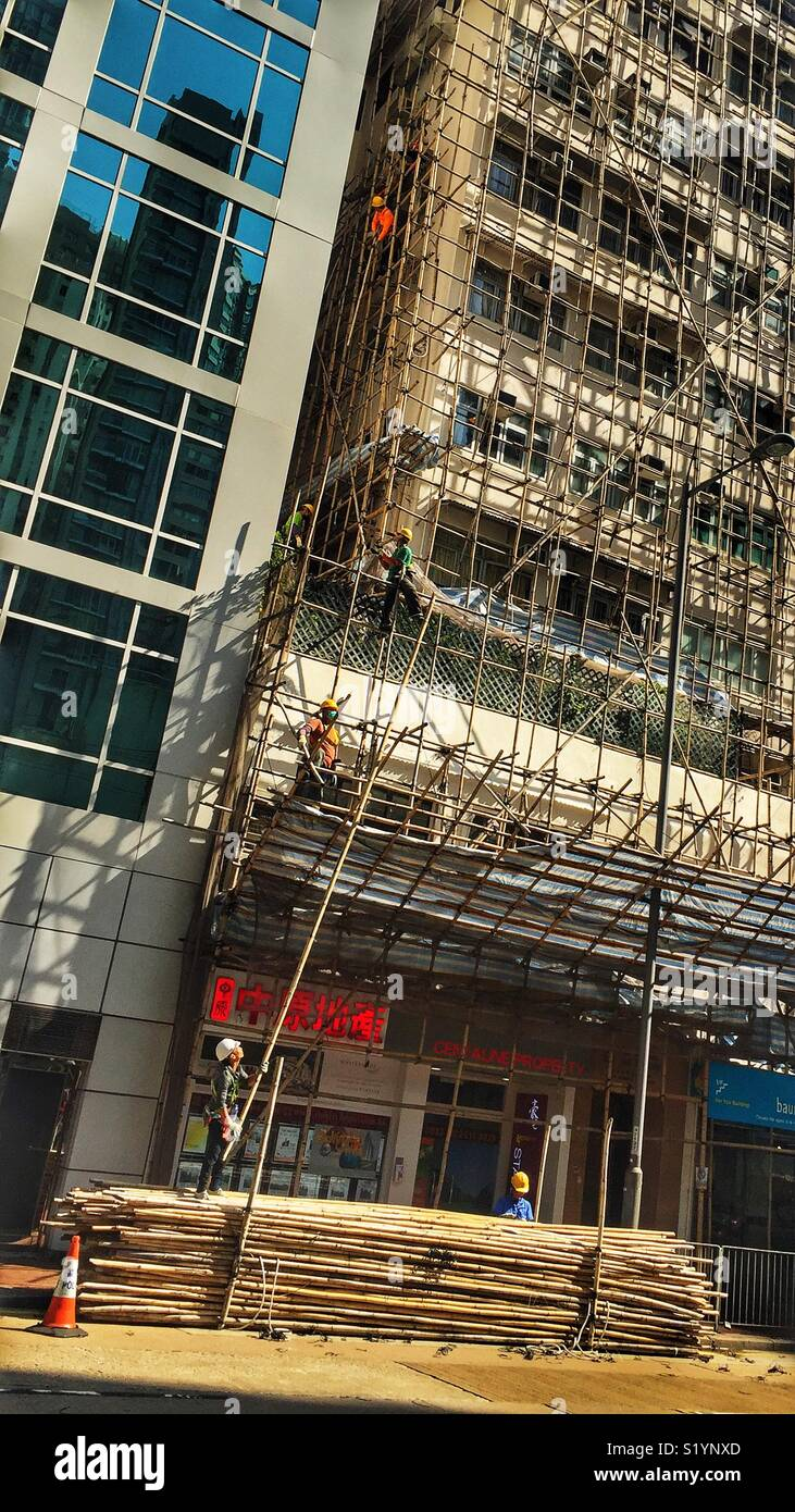 Workers dismantle bamboo scaffolding from a renovated residential highrise building in Wan Chai, Hong Kong Island - Stock Image