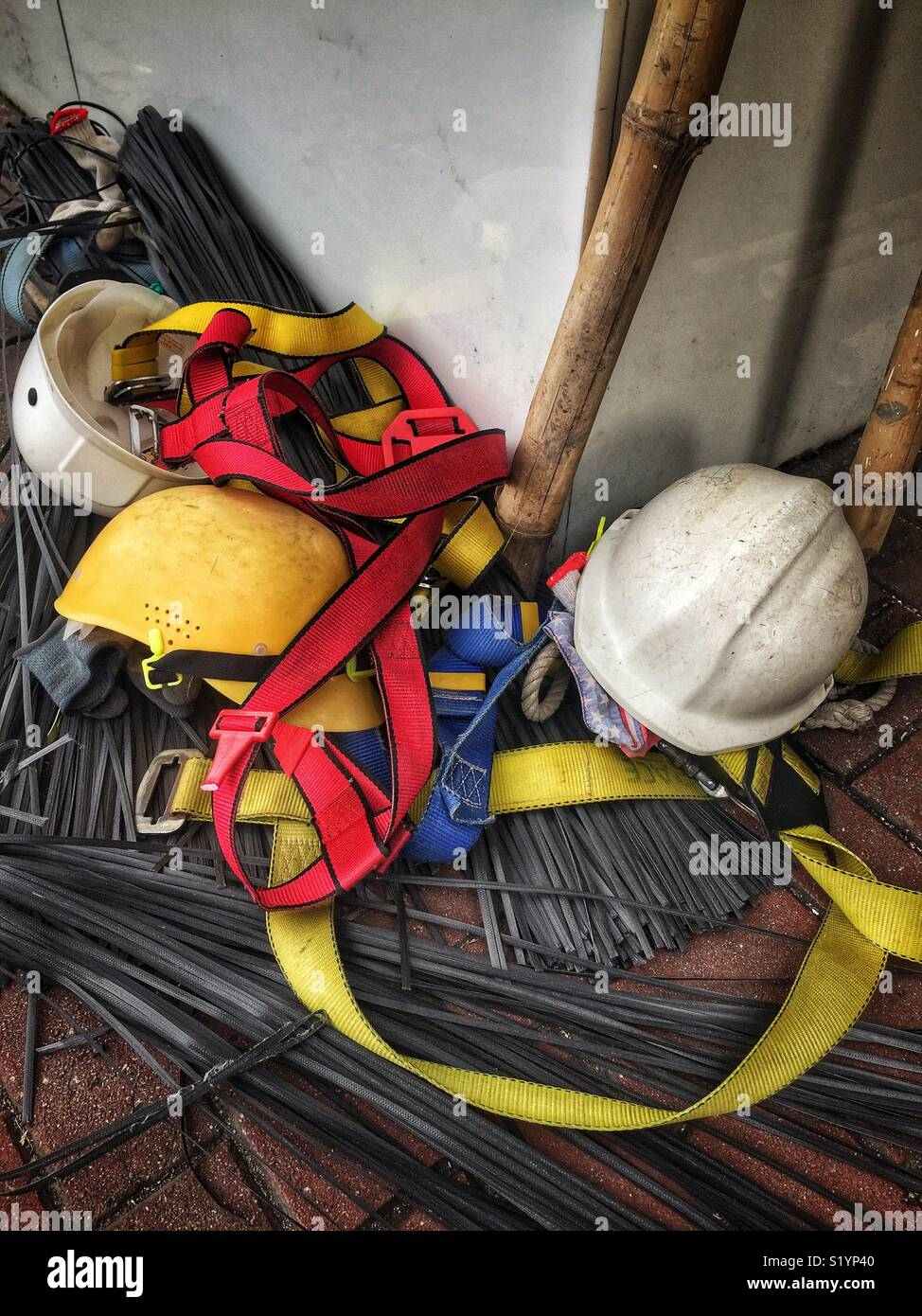 Safety helmets, harnesses and plastic ties used to construct bamboo scaffolding, Wan Chai, Hong Kong Island - Stock Image