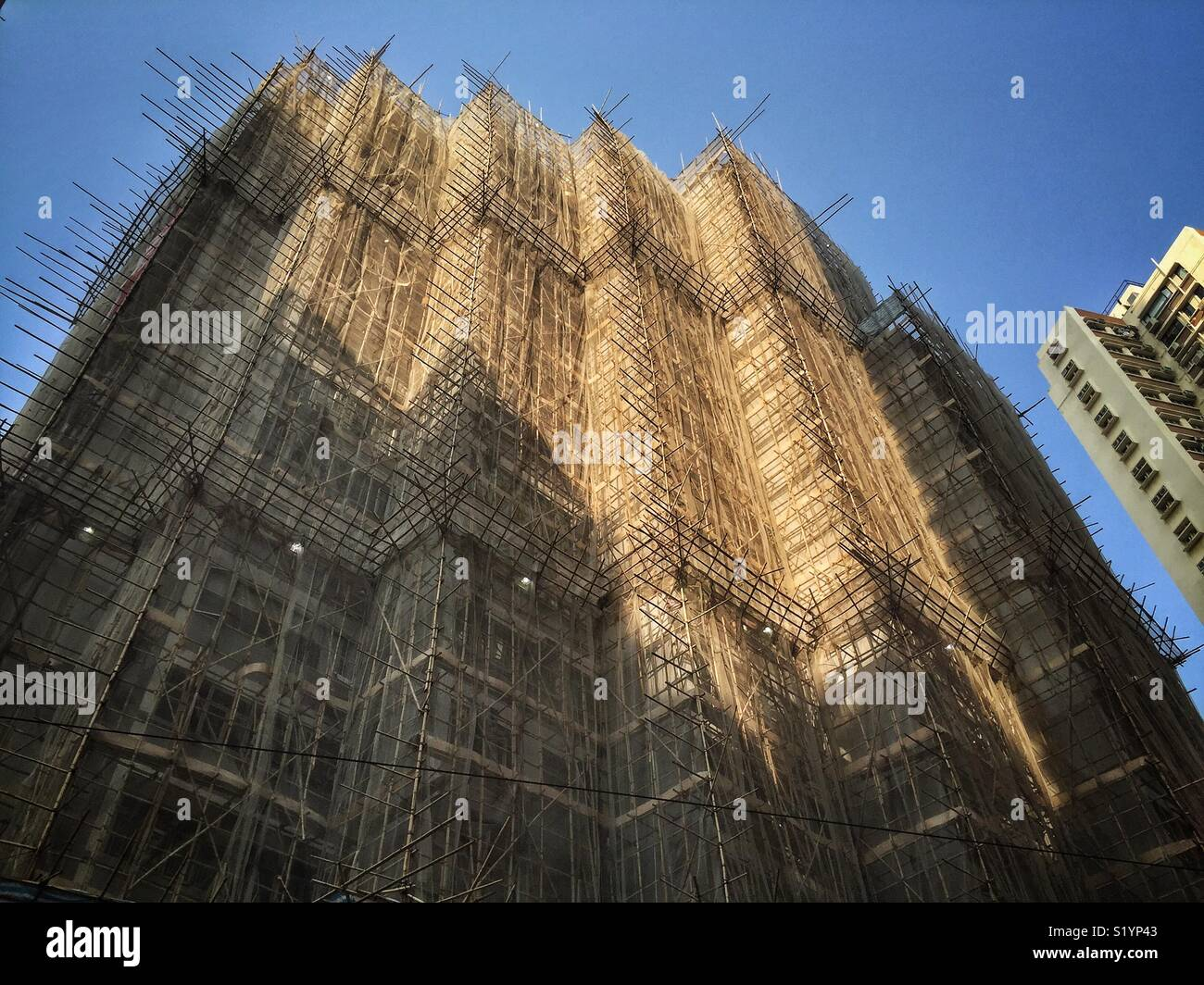 A high-rise residential apartment building covered with bamboo scaffolding in Wan Chai, Hong Kong Island - Stock Image