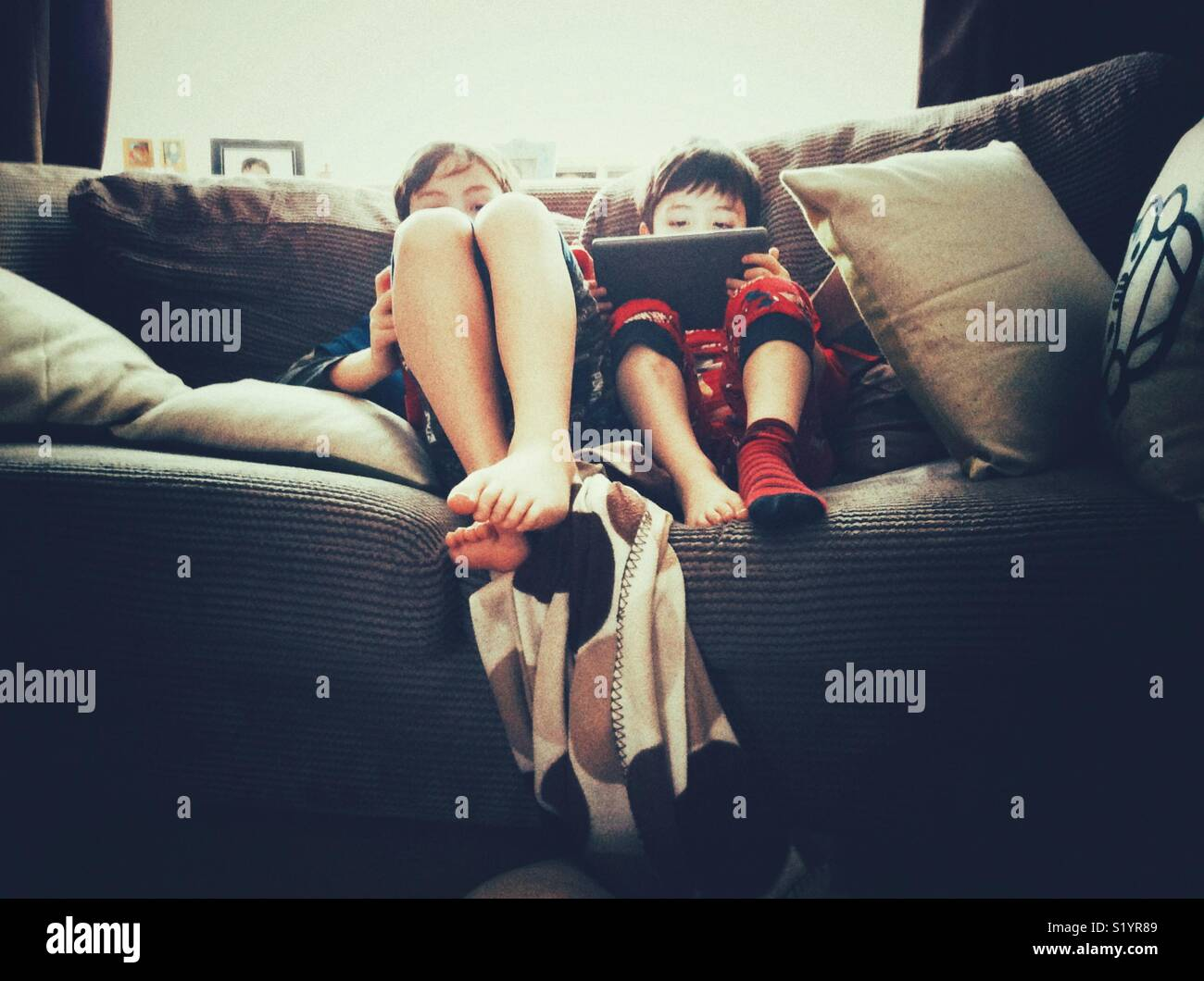 Two young brothers sat together on a sofa playing games on tablet PCs. - Stock Image