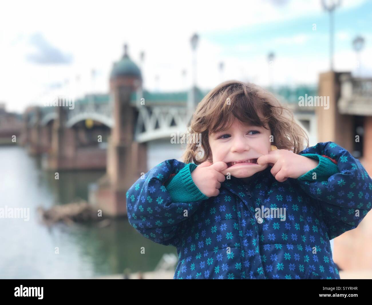 Portrait of little girl grimacing Pont Saint Pierre Toulouse France - Stock Image