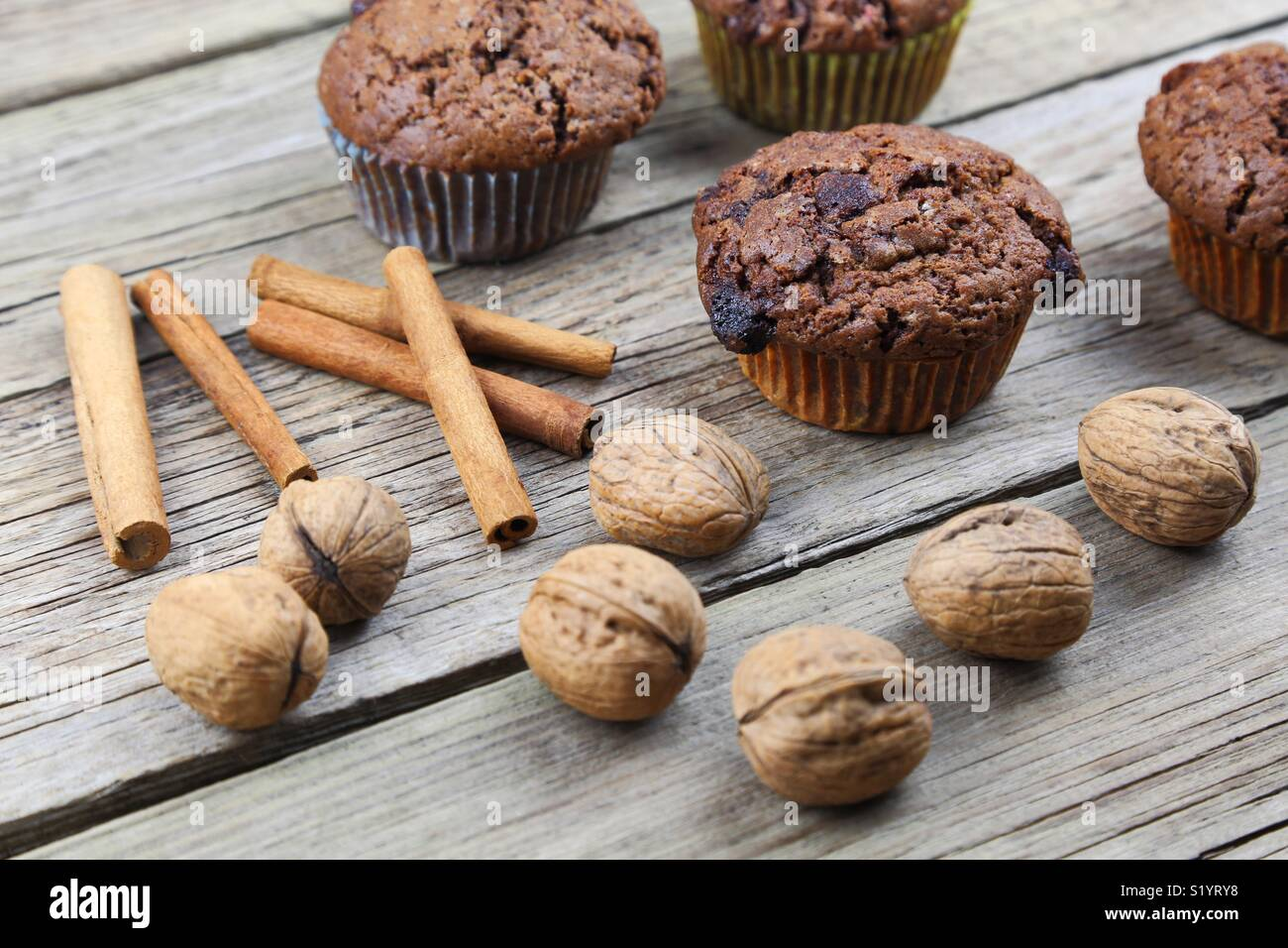 Close up of chocolate muffins on a wooden background - Stock Image