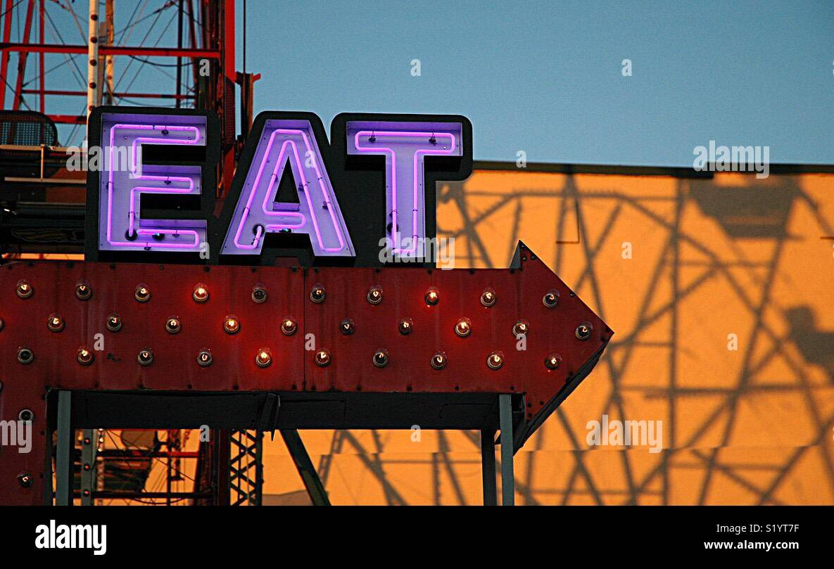 A neon sign in a park entices people to come and eat. - Stock Image