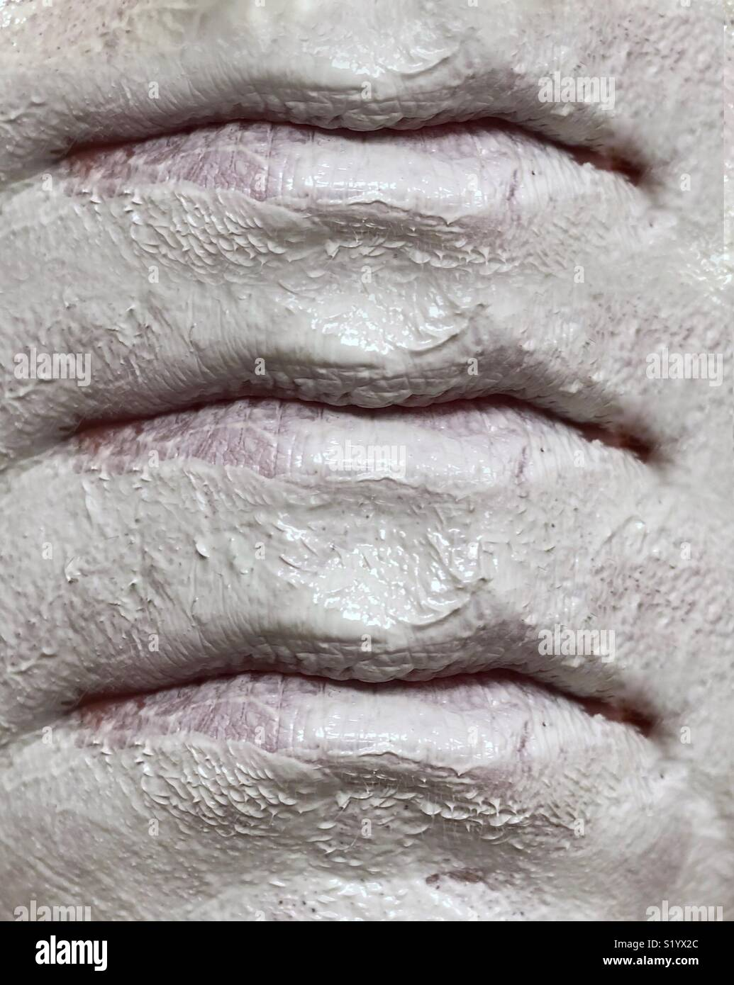 An abstract image of three sets of lips, on a face wearing a white clay mud mask - Stock Image
