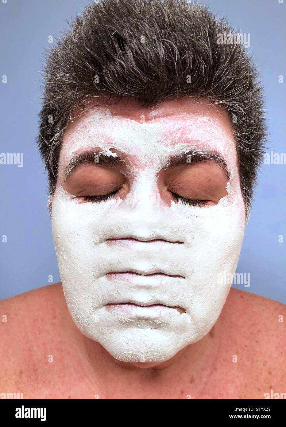 An abstract conceptual artwork of a dark haired. Caucasian woman with her eyes closed wearing a white clay face mask with three sets of lips. - Stock Image