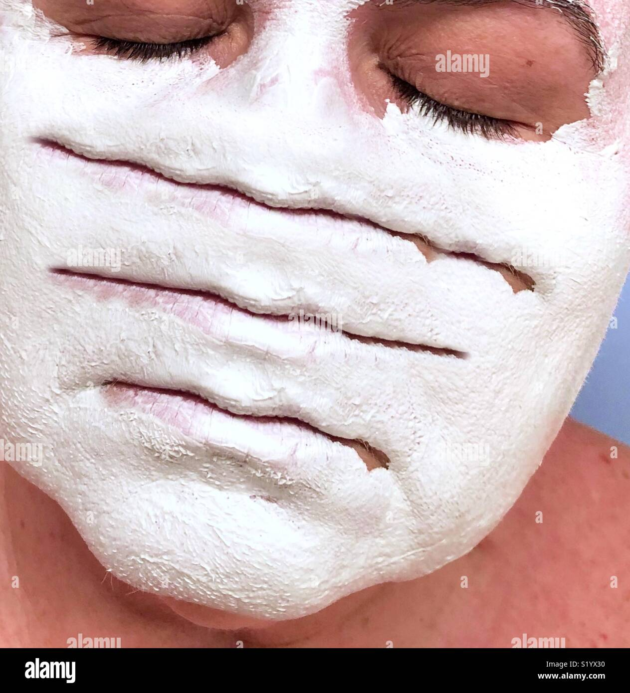 An abstract conceptual artwork of a woman with closed eyes wearing a white clay mud mask with three sets of lips - Stock Image
