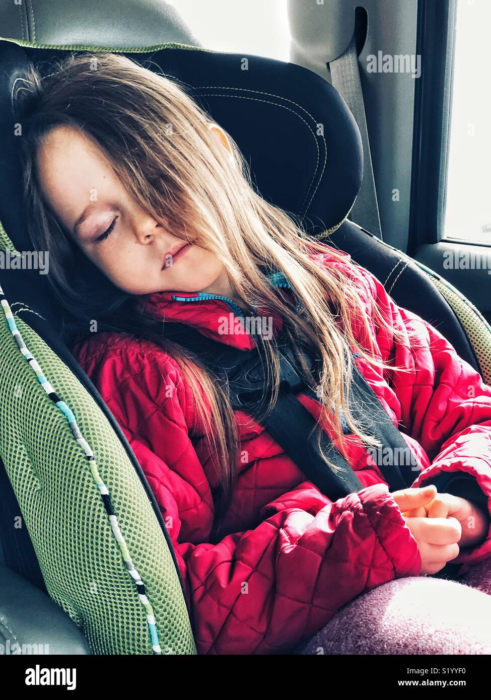 5 Year Old Girl Sleeping In Forward Facing Car Seat With Point Harness And Long Hair Covering Half Her Face