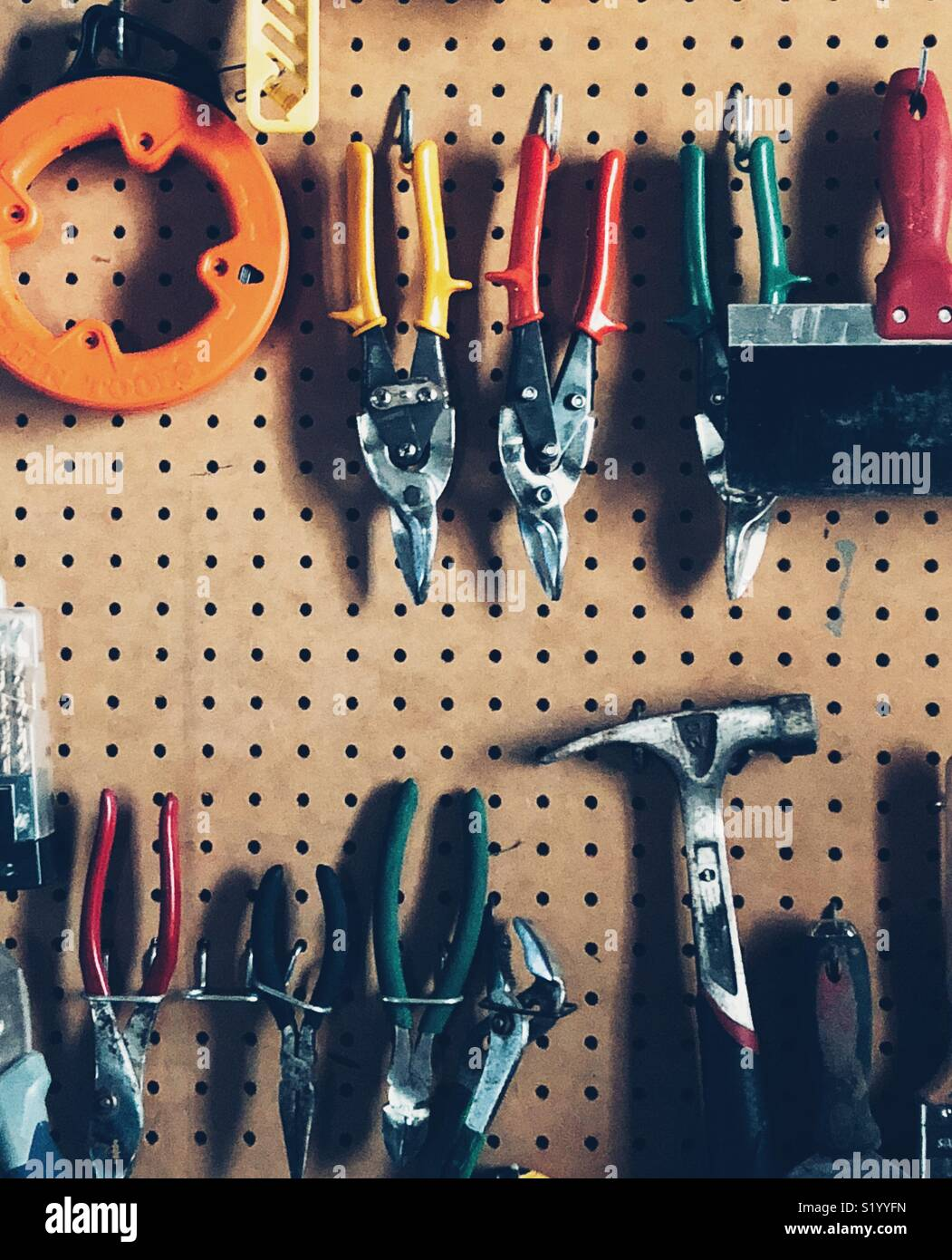 Pegboard full of random tools in a garage - Stock Image