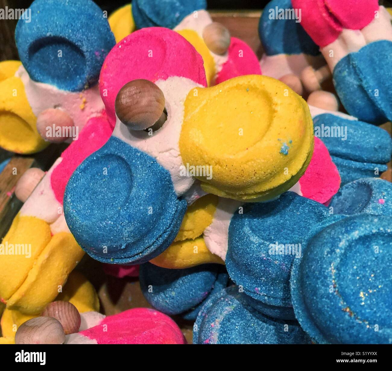 Yellow , blue and magenta bath bomb in shape of fidget  spinner - Stock Image