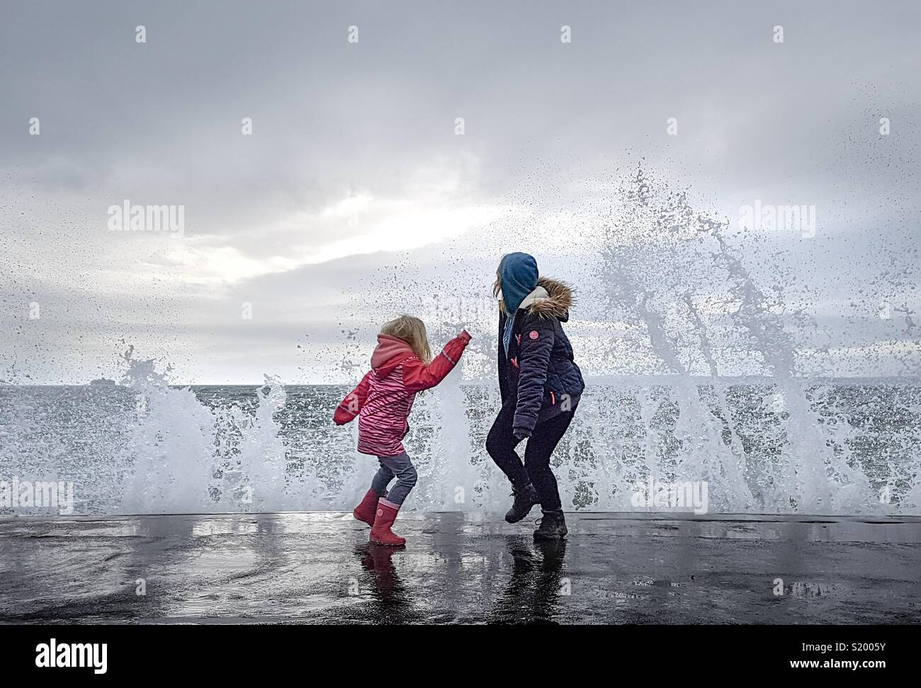 Kids dodging the waves at Southsea - Stock Image