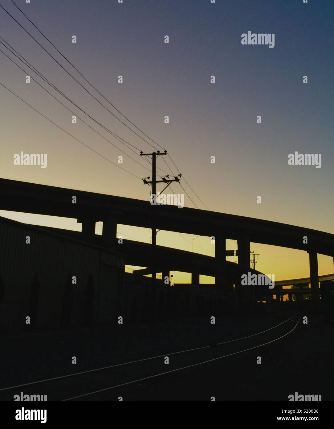 Highway overpasses and cable car tracks at sunset. - Stock Image