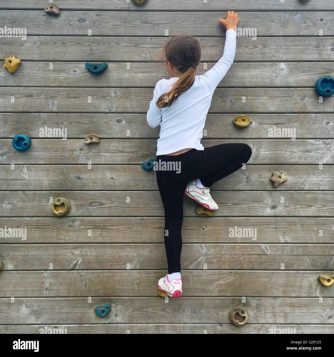 A girl on a playground climbing wall - Stock Image