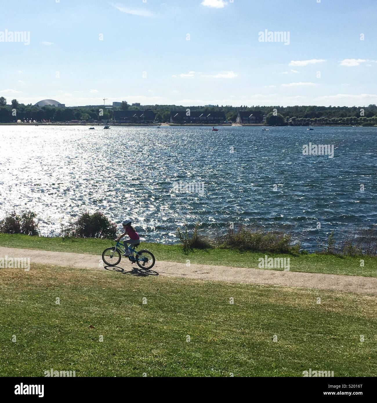 Child cycling around Willen Lake, Milton Keynes, UK - Stock Image