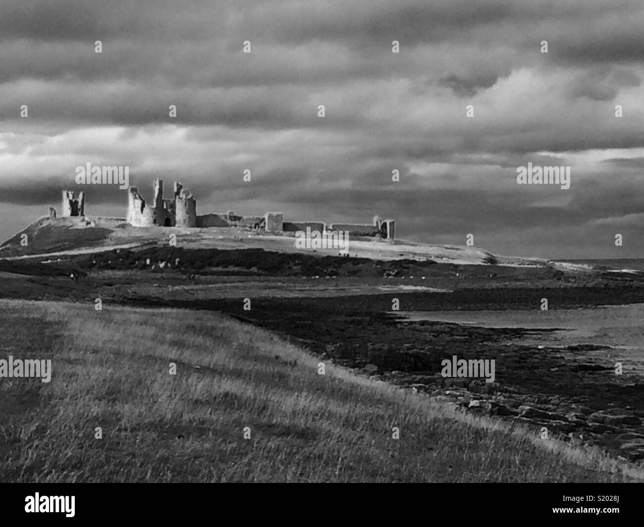 Dunstanburgh castle in black and white - Stock Image