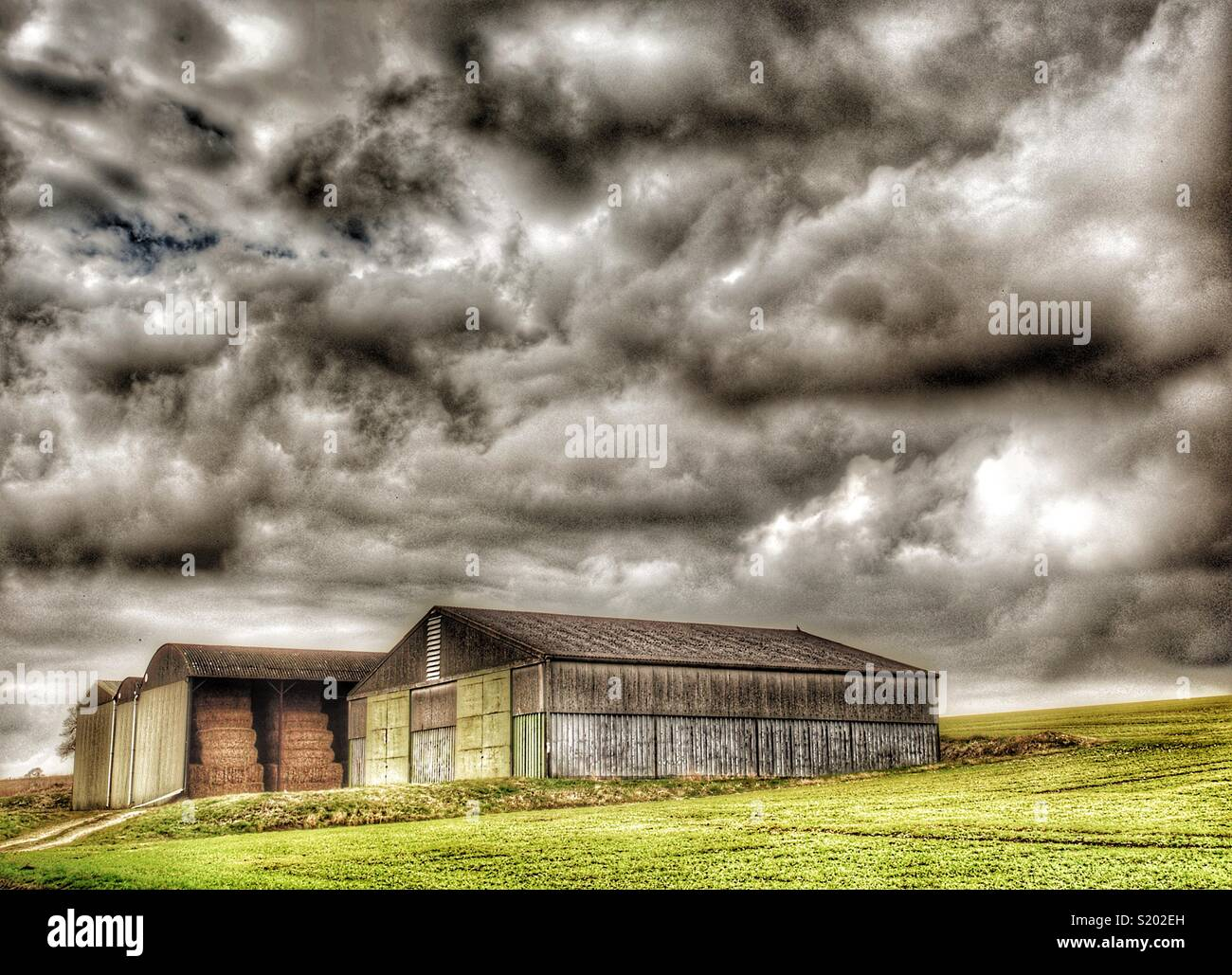 Barns in field with an angry sky, Yorkshire Dales,England, UK Stock Photo