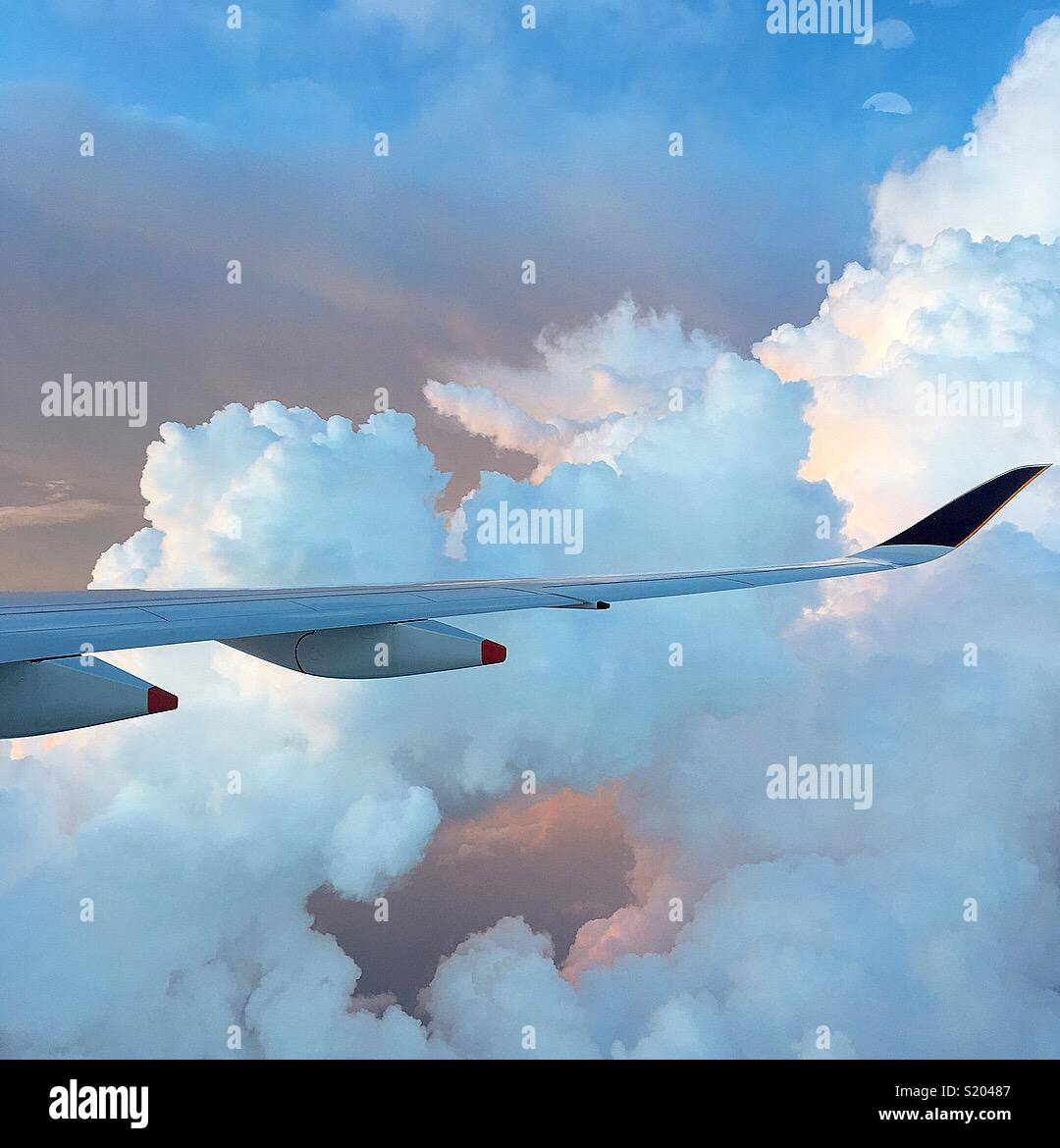 Airplane wing flying through clouds traveling above the South Pacific. - Stock Image