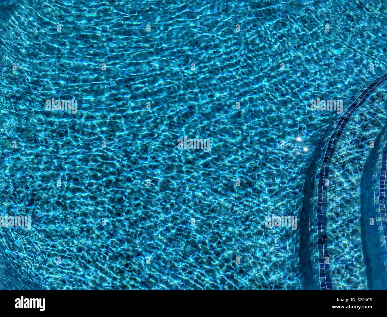 Swimming pool water with ripples on a bright, sunny day - Stock Image