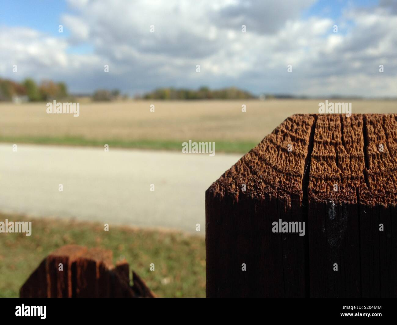 Fence post with field in background. - Stock Image
