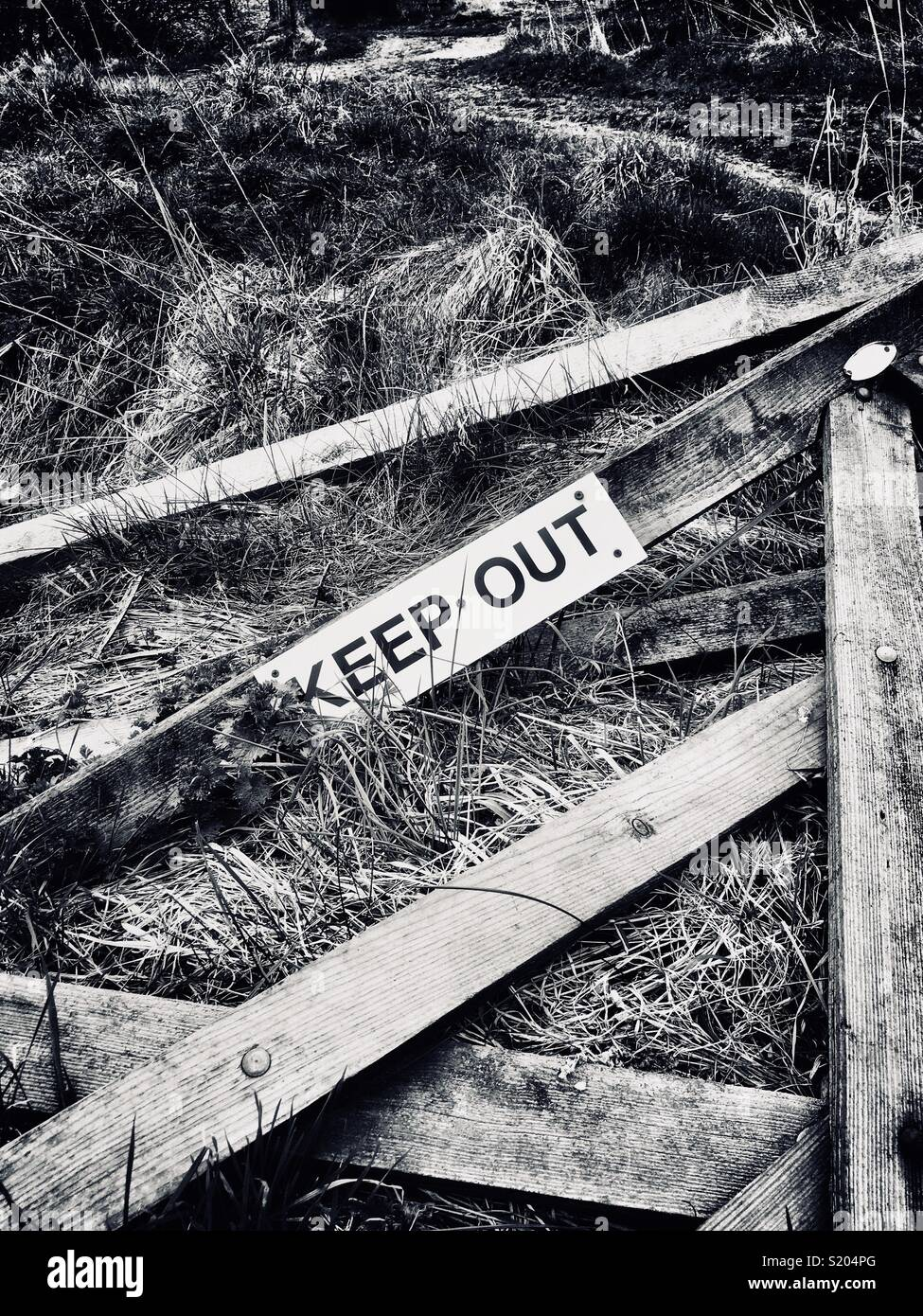 Broken wooden gate on farmland with a keep out sign attached - Stock Image