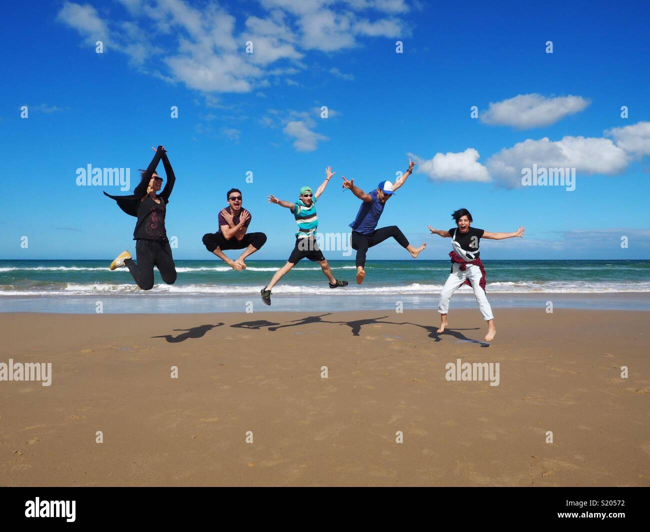 Friends having fun jumping on a beach on a sunny day - Stock Image