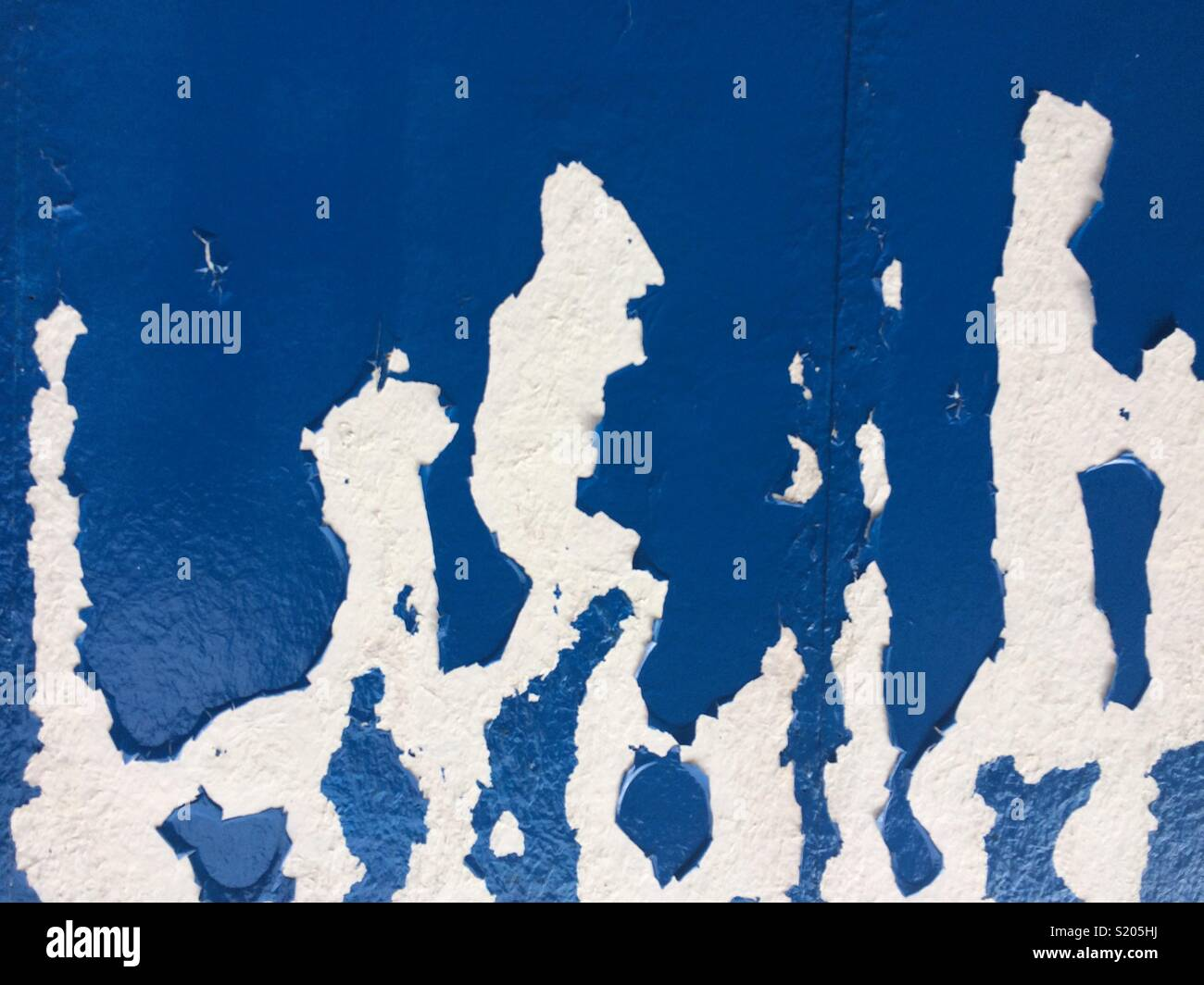 Passers by picture on peeling paint - Stock Image