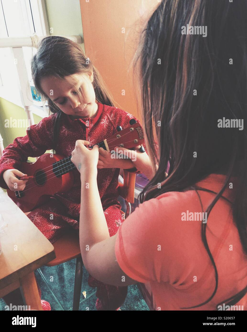 Big sister teaching little sister how to play ukulele - Stock Image