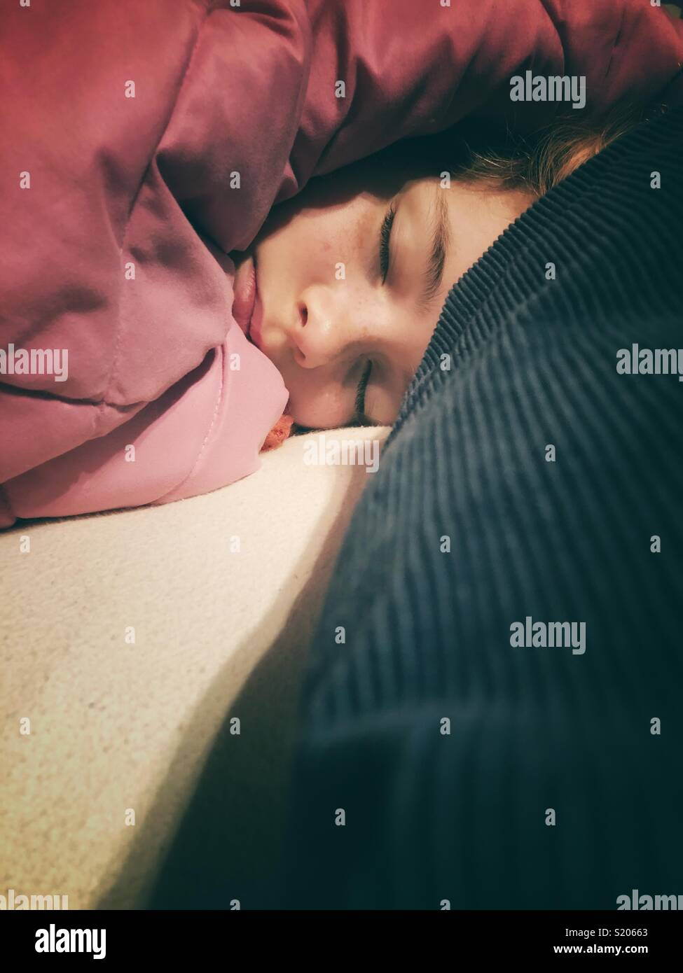 Sleeping girl with pink blanket covering head - Stock Image