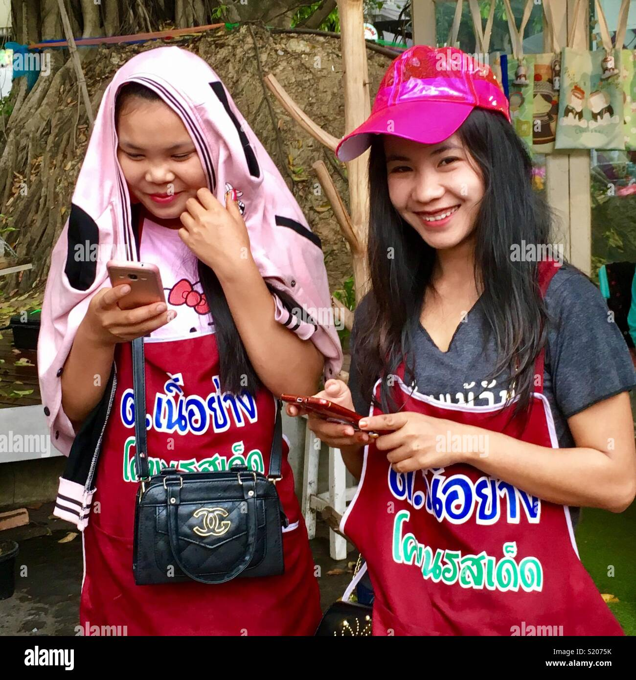 Young Thai salesladies on their mobile phone - Stock Image