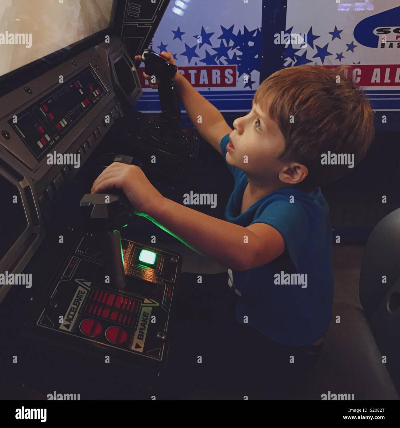 Boy playing arcade game - Stock Image