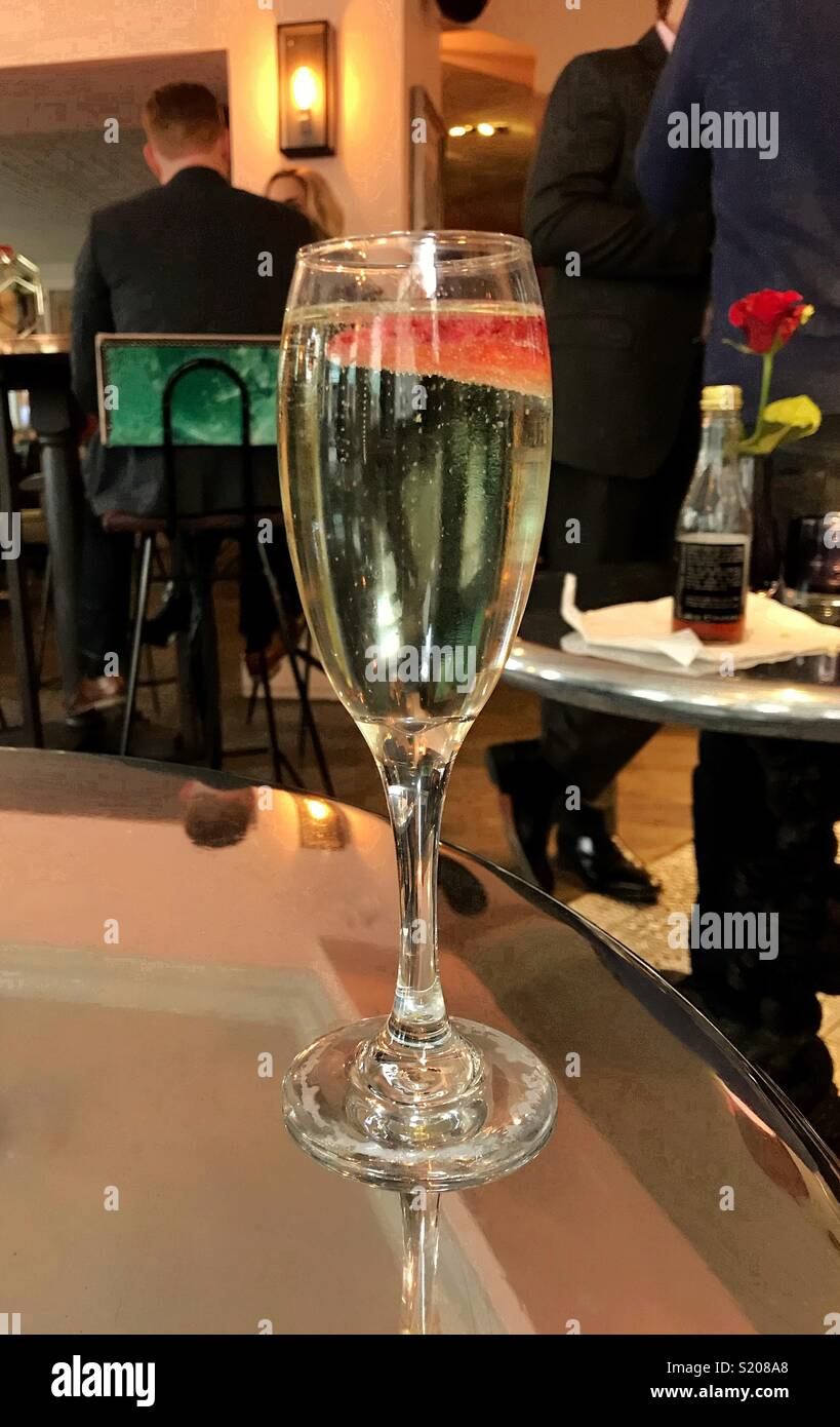 Glass of sparkling wine with a floating strawberry piece - Stock Image