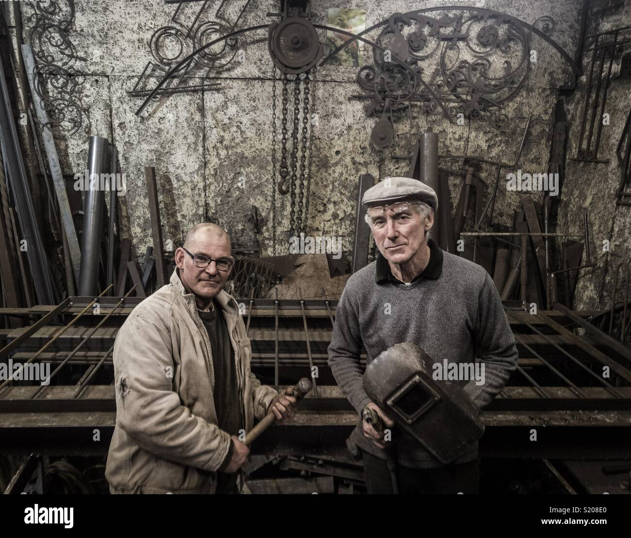 Peter Clutterbuck, Designer Blacksmith and one of his team at his Southsea workshop - Stock Image
