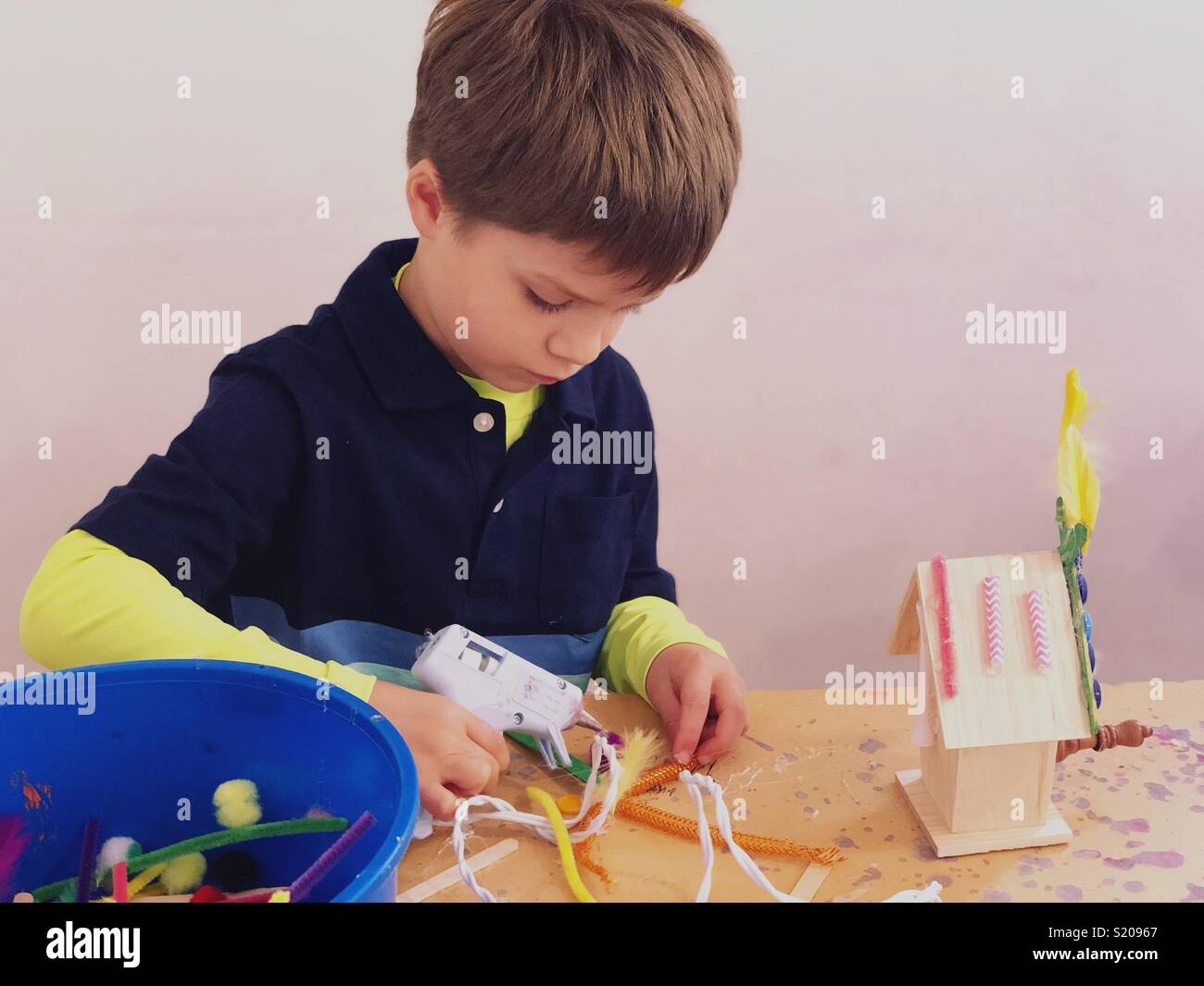 Boy crafting and using glue gun Stock Photo